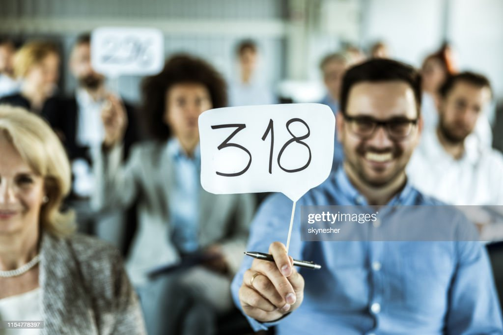 Close up of an auction paddle in businessman's hand. : Stock Photo