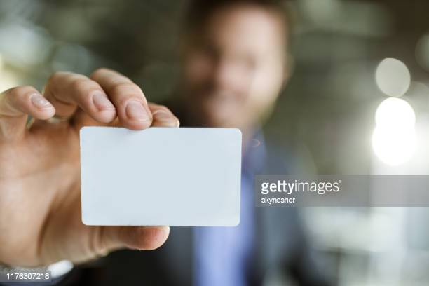 close up of an empty business card in man's hand. - tenere foto e immagini stock