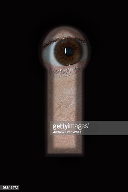 close up of an eye staring through a keyhole