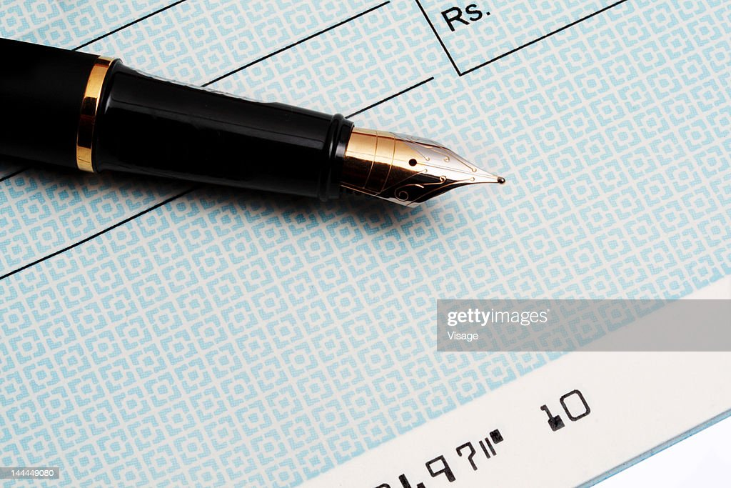 Close up of an ink pen and a cheque : Foto de stock