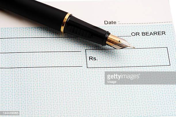 Close up of an ink pen and a cheque