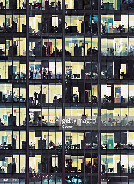 close up of an office building at night with business executives working late - bürogebäude stock-fotos und bilder