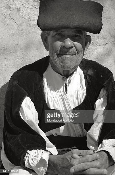 Close up of an old Sardinian shepherd who is wearing the traditional clothes a shirt closed with two silver bottons and a folded beret on his head...