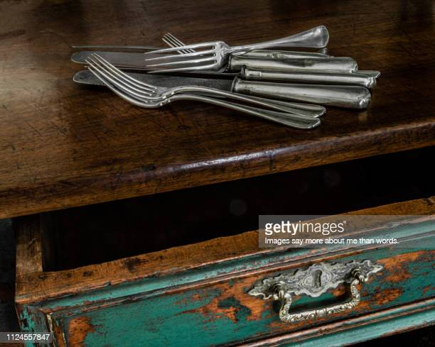 a close up of an old table with many silverware on it. still life. - eating utensil stock pictures, royalty-free photos & images