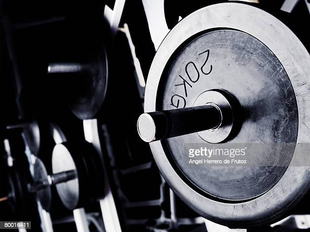 close up of an olympic bench bar and weight plates on a rack inside a gimnasium.  selective focus on foreground. barcelona 2008. - kilogram stock pictures, royalty-free photos & images