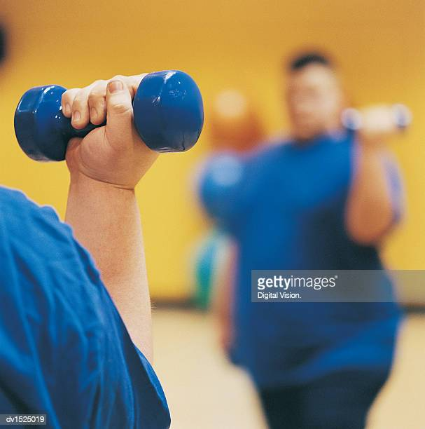 Close Up of an Overweight Man Weight Training in a Gym