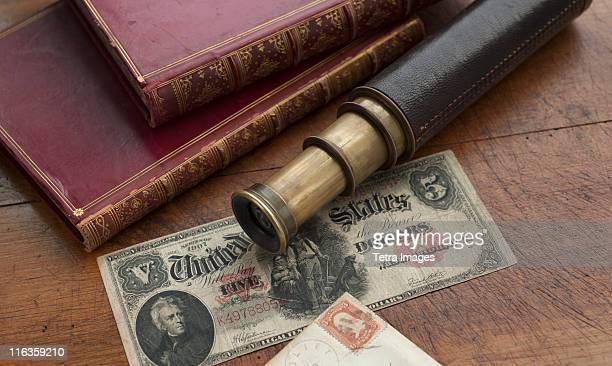 Close up of antique telescope, books and banknote