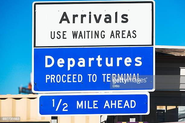 Close up of arrival and departure road direction sign outside airport terminal building, New York, USA