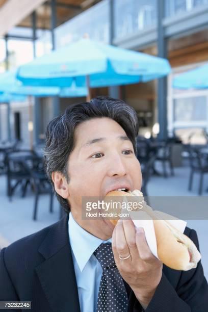 Close up of Asian businessman eating hot dog outdoors