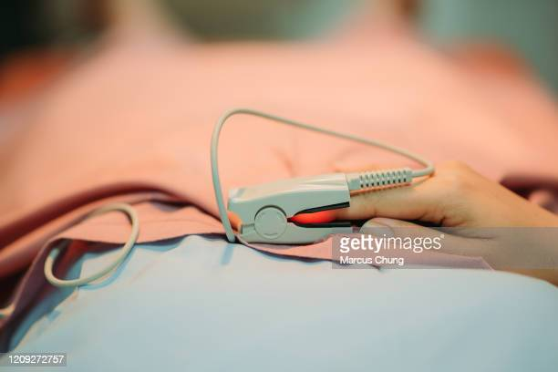 close up of asian chinese female patient doing heart rate test by pulse oxymeter while lying down on bed at operating theatre in hospital - pulse oximeter stock pictures, royalty-free photos & images