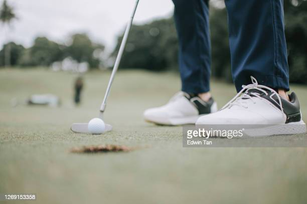 close up of asian chinese male golfer tapping in the ball to a golf hole on the golf course - putting stock pictures, royalty-free photos & images