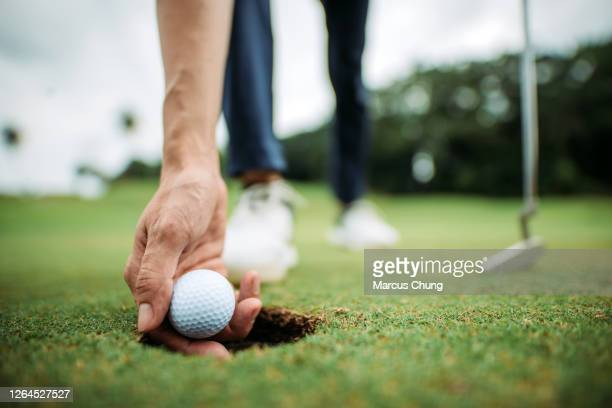 close up of asian chinese young male golfer picking up golf ball with hand at the hole of golf course - individual event stock pictures, royalty-free photos & images