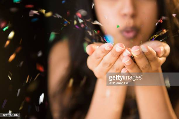 Close up of Asian woman blowing confetti from hands