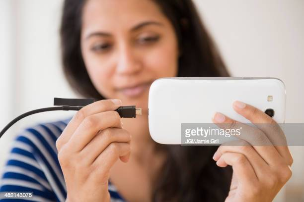 Close up of Asian woman connecting cell phone to battery