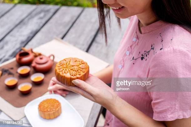 close up of asian woman holding tasty mooncake with chinese tea set on table, celebrating moon cake festival - moon cake stock pictures, royalty-free photos & images