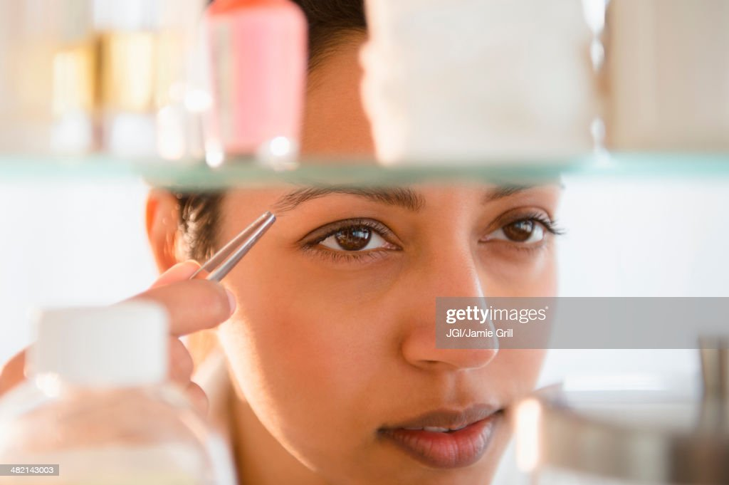 Close up of Asian woman tweezing eyebrows : Stock Photo
