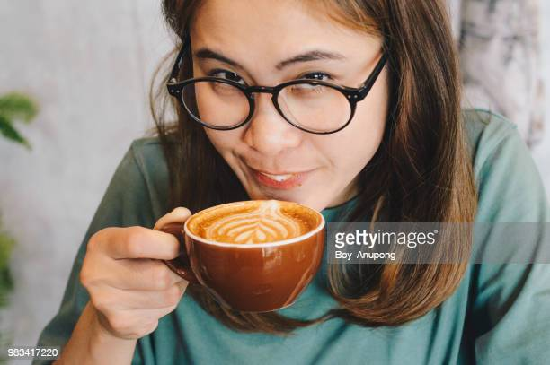 Close up of Asian women drinking hot latte coffee in the cafe and looking to the camera.