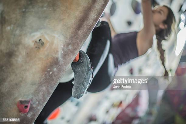 Close up of athlete climbing rock wall in gym