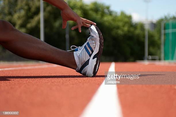 close up of athlete stretching on track - aufwärmen stock-fotos und bilder