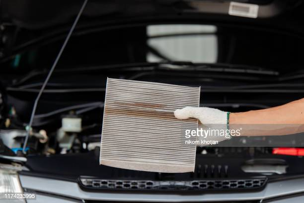 close up of auto mechanic hands checking an air filter in garage. - spare part stock pictures, royalty-free photos & images