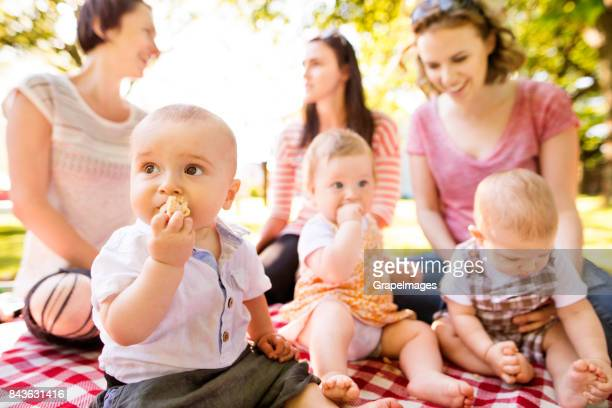 close up of baby boy in public park, mothers with babies in the background. - group of objects stock photos and pictures