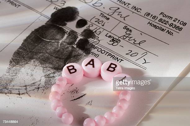 close up of baby bracelet and birth certificate - birth certificate stock pictures, royalty-free photos & images