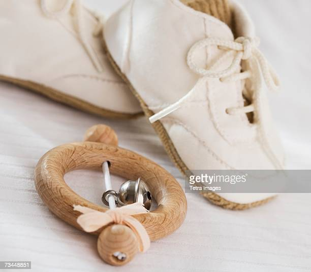 close up of baby rattle and baby shoes - toy rattle stock pictures, royalty-free photos & images