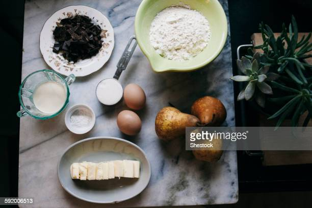 Close up of baking ingredients and pears on marble counter