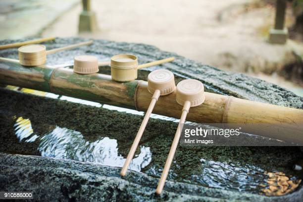 close up of bamboo water hand washing basins at shinto sakurai shrine, fukuoka, japan. - shinto shrine stock pictures, royalty-free photos & images