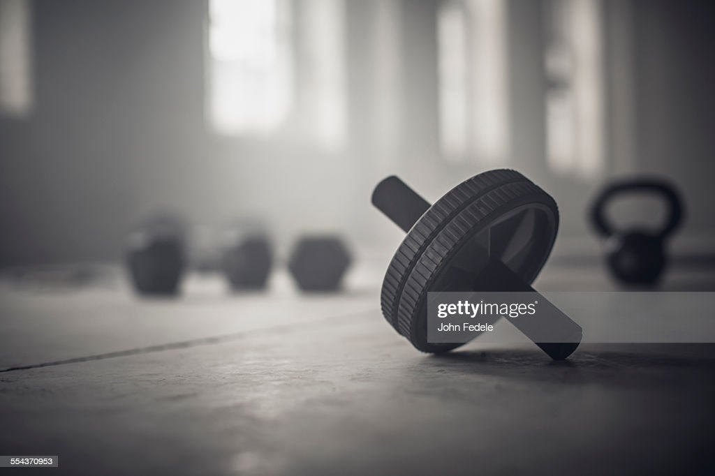 Close up of barbell weights on floor of dark gym : Stock Photo