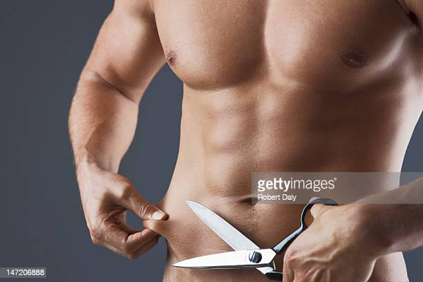Close up of bare chested man holding scissors and squeezing stomach