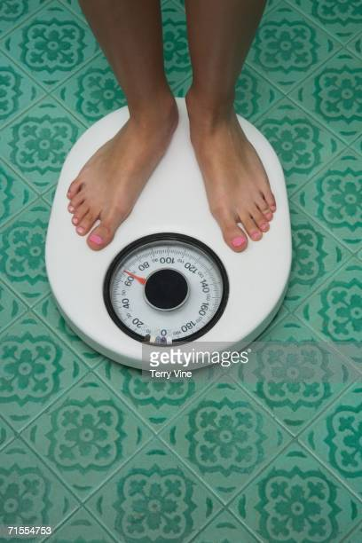 close up of bare feet on bathroom scale - pretty asian feet stock photos and pictures