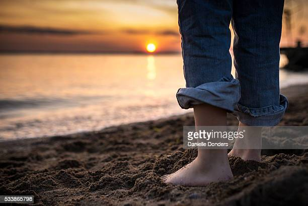 """close up of bare feet on the beach at sunset - """"danielle donders"""" stock pictures, royalty-free photos & images"""