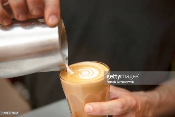 Close up of baristas hands pouring milk into coffee in cafe