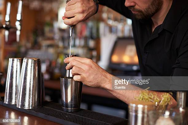 Close Up Of Barman Mixing Cocktail On Counter