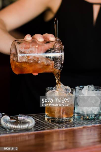 close up of bartender hands making a cocktail alcoholic drink at a bar counter - buffalo new york state stock pictures, royalty-free photos & images