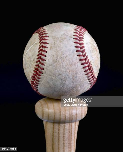 Close Up Of Base Ball Over Stick Against Wooden Wall