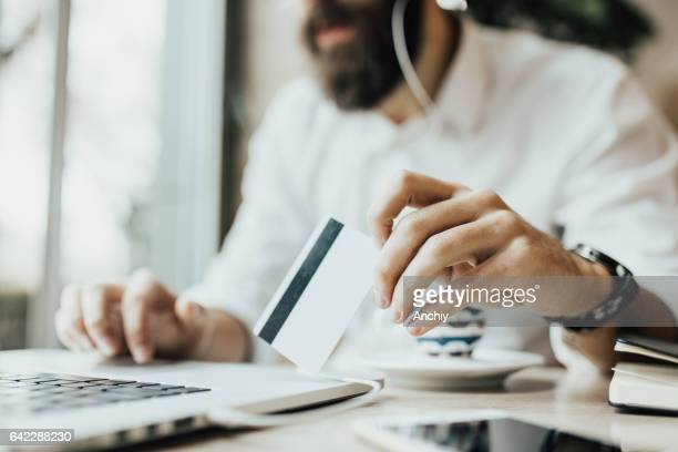 Close up of bearded hipster holding online shopping card