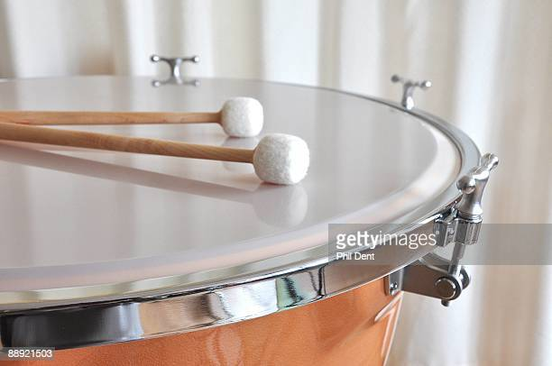 Close up of beater drum stocks resting on the skin of a timpani drum showing tuning lugs