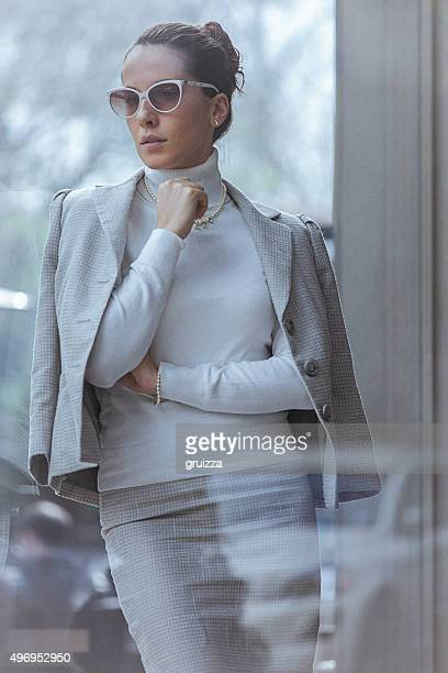 Close up of beautiful, elegant woman, leaning against the window