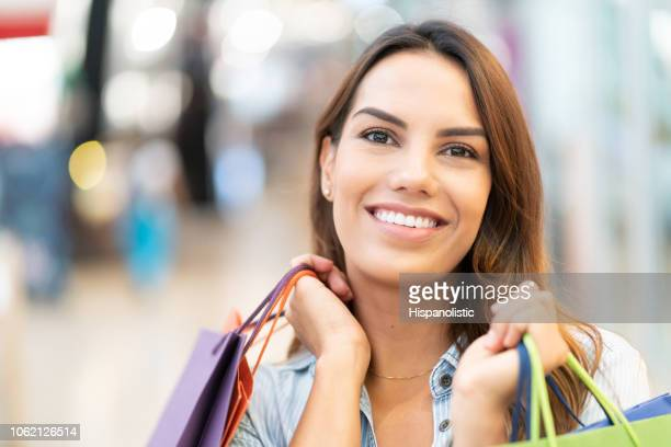 close up of beautiful latin american woman holding shopping bags and looking at camera very happy - hispanolistic stock photos and pictures