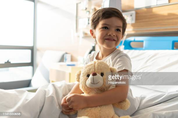 close up of beautiful little boy hugging his teddy bear while looking away daydreaming - child hospital stock pictures, royalty-free photos & images