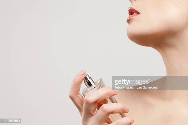 Close up of beautiful young woman spraying perfumes,  studio shot