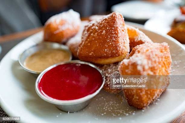 Close up of beignet donuts with raspberry dipping sauce on a white plate sprinkled with powdered sugar San Francisco California January 22 2017
