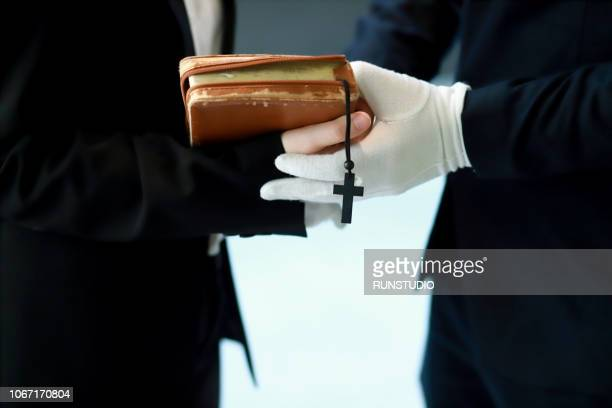 close up of bereaved holding bible - crematorium stock pictures, royalty-free photos & images