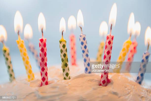 close up of birthday candles in cake - birthday candles stock photos and pictures