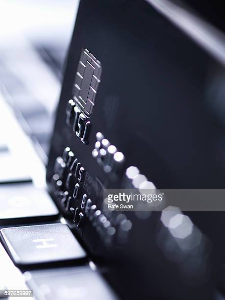 Close up of black credit card standing on computer keyboard