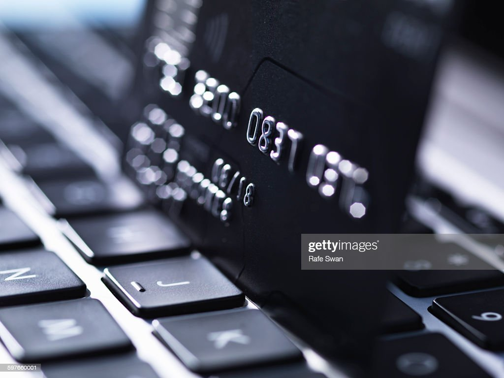 Close up of black credit card standing on computer keyboard : Stock Photo