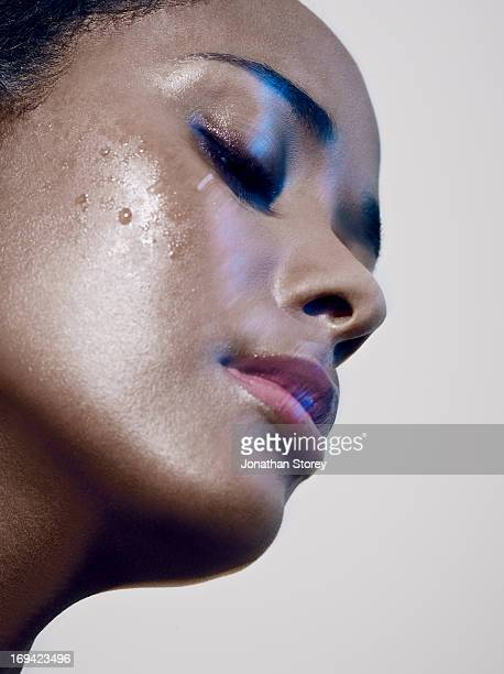 close up of black females face with water on cheak