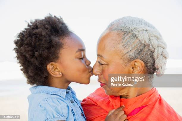 Close up of black granddaughter kissing nose of grandmother